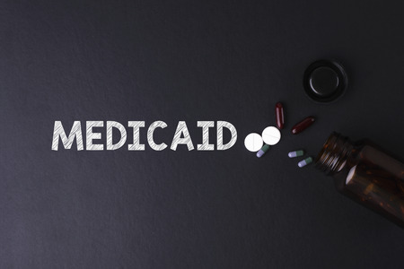 medicaid: MEDICAID word with medicine and bottle - Health concept. Medical conceptual