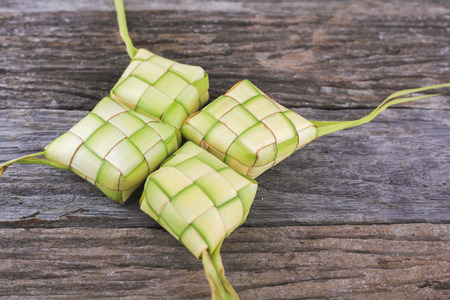 the casing: Ketupat (Rice Dumpling) On Wooden Background. Ketupat is a natural rice casing made from young coconut leaves for cooking rice during eid Mubarak Stock Photo