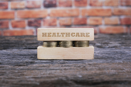 healthy economy: Business Concept - HEALTHCARE word Golden coin stacked with wooden bar on shallow brick background Stock Photo