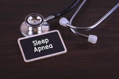 somnambulism: Medical Concept- Sleep Apnea words written on label tag with Stethoscope on wood background
