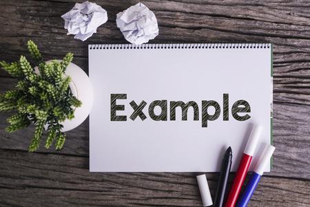 Blocco note e pianta verde su sfondo in legno con la parola Esempio