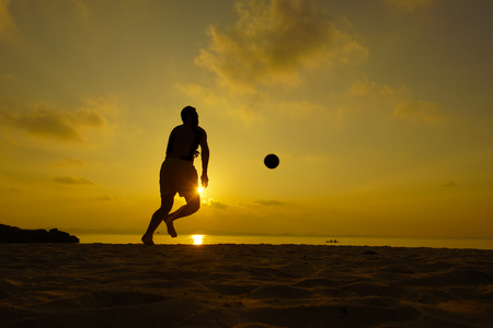 perhentian: Silhouettes of footballers on the sunset sky