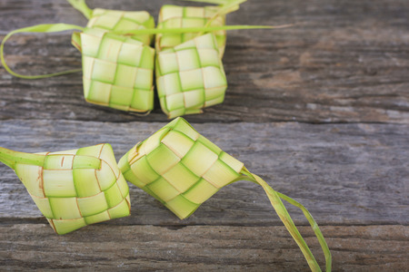 local festivals: Ketupat (Rice Dumpling) On Wooden Background. Ketupat is a natural rice casing made from young coconut leaves for cooking rice during eid Mubarak Stock Photo
