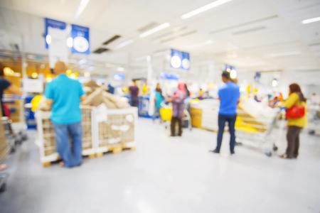 Blur image view of cashier with a line of people at the check-out counter Stock Photo