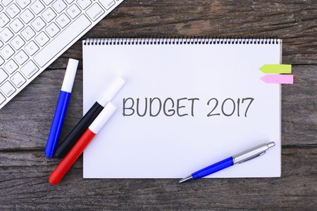Notebook with BUDGET 2017 Handwritten on wooden background and Modern Computer Keyboard. Top View Composition Stock Photo