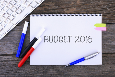 marginal returns: Notebook with BUDGET 2016 Handwritten on wooden background and Modern Computer Keyboard. Top View Composition
