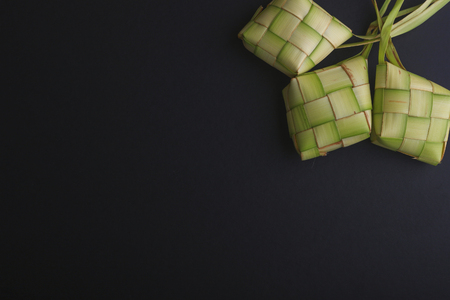 the casing: Ketupat (Rice Dumpling) On Black Background. Ketupat is a natural rice casing made from young coconut leaves for cooking rice during eid Mubarak