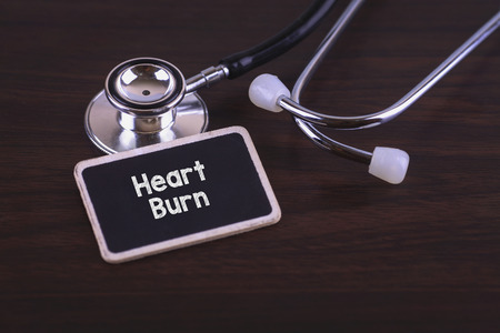 gastro: Medical Concept- Heart Burn words written on label tag with Stethoscope on wood background Stock Photo