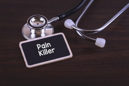 opioid: Medical Concept- Pain Killer words written on label tag with Stethoscope on wood background