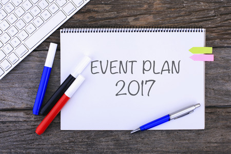 a meeting with a view to marriage: Notebook with EVENT PLAN 2017 Handwritten on wooden background and Modern Computer Keyboard. Top View Composition