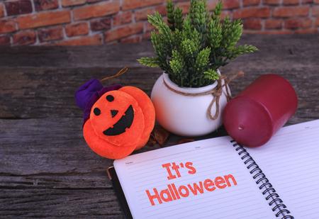 adn: Pumpkin Head ,Candle adn a Notebook written Its Halloween on wooden background