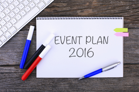 coordinating: Notebook with EVENT PLAN 2016 Handwritten on wooden background and Modern Computer Keyboard. Top View Composition