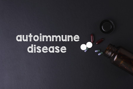 crohn's disease: Autoimmune Disease word with medicine and bottle - Health concept. Medical conceptual Stock Photo