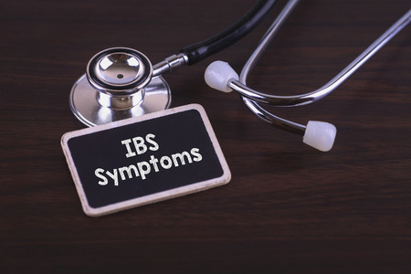 ibs: Medical Concept- IBS Symptoms words written on label tag with Stethoscope on wood background