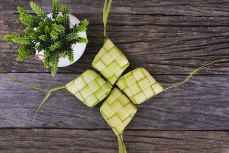Ketupat (rijstbol) op houten achtergrond. Ketupat is een natuurlijke rijstkom gemaakt van jonge kokosnootbladeren voor het koken van rijst tijdens eid Mubarak