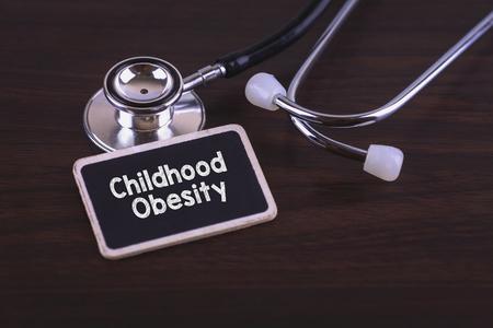 obesidad infantil: palabras médica Concepto-obesidad de la niñez escritas en la etiqueta de la etiqueta con el estetoscopio en el fondo de madera