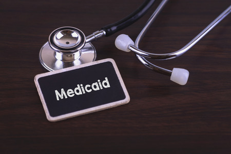 medicaid: Medical Concept- Medicaid words written on label tag with Stethoscope on wood background Stock Photo