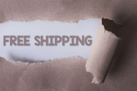 unbound: torn paper with FREE SHIPPING word. Copyspace area.