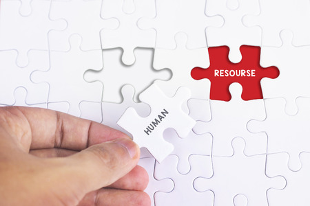 resourse: Business Concept - Female hand and missing puzzle with HUMAN AND RESOURSE WORD Stock Photo