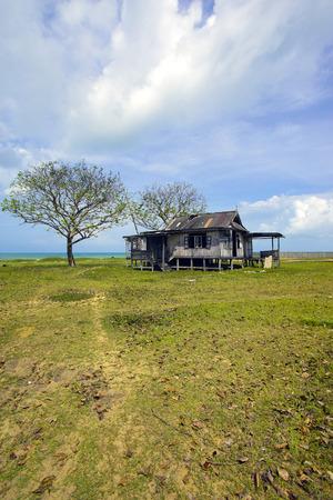 Old abandoned house under blue sky near the beach Stock Photo