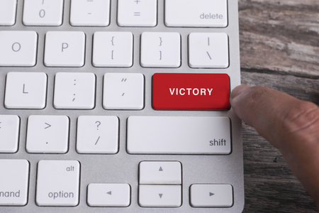 libertarian: Close up of finger on keyboard button with VICTORY word