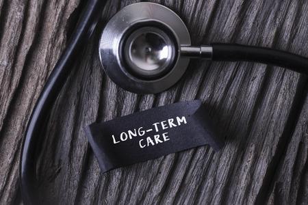 pflegeversicherung: Medical Konzept- PFLEGEBEDÜRFTIGKEIT Wort auf Label-Tag mit Stethoskop geschrieben auf Holz Hintergrund Lizenzfreie Bilder