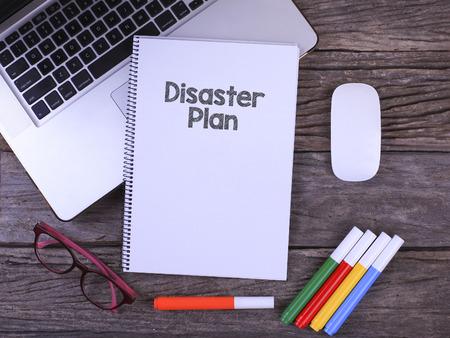 """Werkruimte op kantoor met laptop, koffiekopje, bril, Notebook schrijven """"Disaster Plan"""" op tafel Stockfoto"""