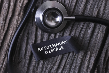 autoimmune: Medical Concept- AUTOIMMUNE DISEASE word written on label tag with Stethoscope on wood background