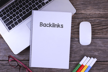 linkbuilding: Working space at the office with laptop ,coffee cup,glasses, Notebook writing Backlinks on table