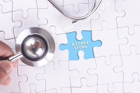 renal stone: Doctor holding a Stethoscope on missing puzzle WITH KIDNEY STONE WORD Stock Photo