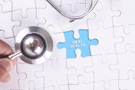 oral health: Doctor holding a Stethoscope on missing puzzle WITH ORAL HEALTH WORD