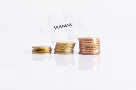 summons: White missing puzzle and gold coins with summons,copyspace area Stock Photo