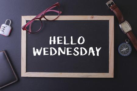 HELLO WEDNESDAY WORD ON BLACKBOARD WITH WATCH,PASPORT, GLASS AND LOCK Stock Photo