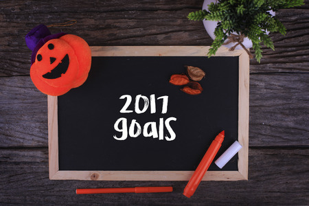 initiatives: Pumpkin Head ,Candle and a Chalkboard written 2017 goals on wooden background Stock Photo