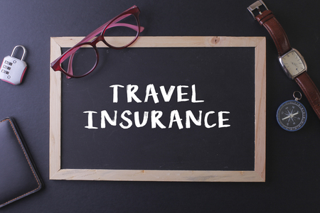 insurer: TRAVEL INSURANCE WORD ON BLACKBOARD WITH WATCH,PASPORT, GLASS AND LOCK