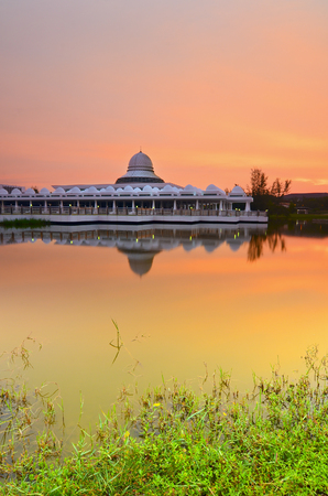 Beautiful white mosque during burning sunrise with mirror reflection on the lake. Vibrant colours