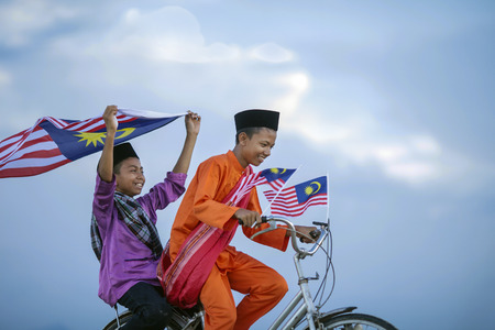 malay village: Independence Day concept - Two happy young local boy riding old bicycle at paddy field holding a Malaysian flag