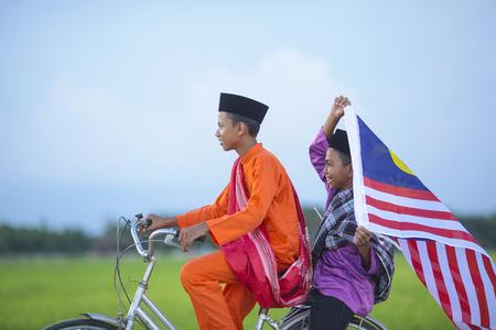 Twee gelukkige jonge lokale jongen die oude fiets berijden bij padiegebied met Maleise vlag - Indepence-Dagconcept