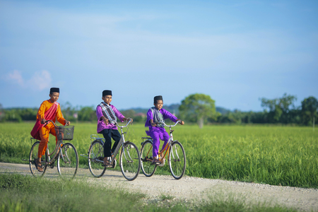 malay boy: Three happy young local boy riding old bicycle at paddy field. Stock Photo