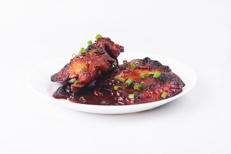 Grilled chicken or ayam golek on white plate, white background. Malaysian traditional cuisine Stock Photo