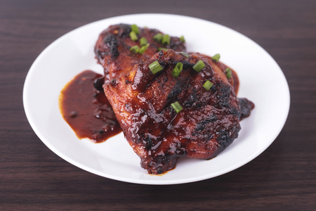 Grilled chicken or ayam golek on white plate, wooden background. Malaysian traditional cuisine Stock Photo