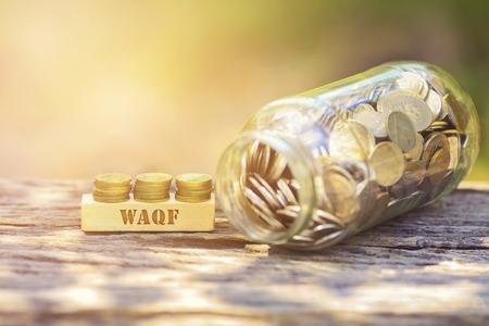 WAQF WORD Gouden die muntstuk met houten bar op ondiepe DOF groene achtergrond wordt gestapeld