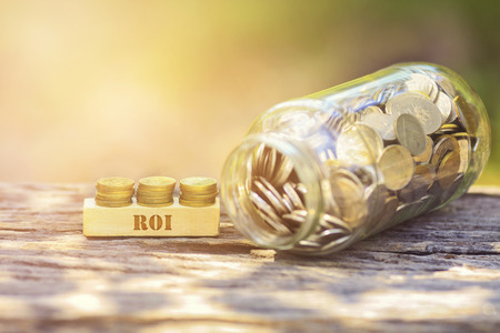 ROI WORD Golden coin stacked with wooden bar on shallow DOF green background Stock Photo