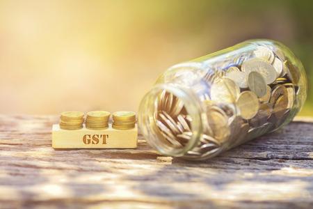 moneda de GST palabra de oro apilado con barra de madera sobre fondo verde DOF