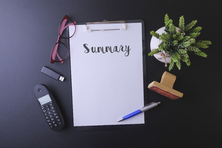 """cuadro sinoptico: Cuaderno de escritura """"Resumen"""" en la tabla, Espacio de trabajo en la oficina con teléfono celular, una unidad USB, gafas y planta verde"""