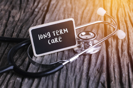 Stethoscope on wood with long term care word as medical concept. Stock fotó