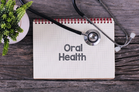 oral health: Oral Health word on notebook,stethoscope and green plan