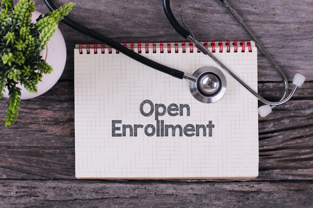 Open Enrollment word on notebook,stethoscope and green plan