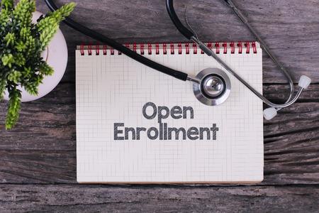Open Inschrijving woord over notebook, stethoscoop en groene plannen Stockfoto