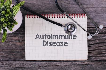 Auto-immuunziektewoord op notitieboekje, stethoscoop en groen plan